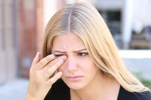 girl rubbing eye ball with finger