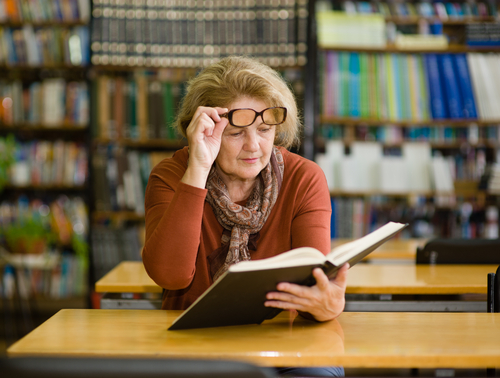 Women reading book with glasses off face.