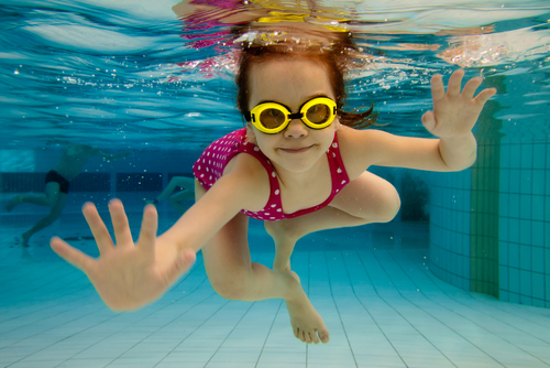 girl swimming with yellow goggles